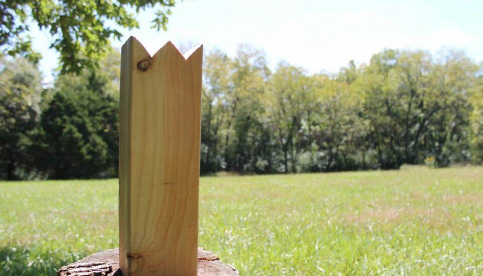 A Kubb king sitting in a field